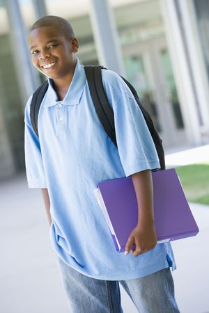 knap sack: Student standing outside school holding binder and smiling (selective focus)