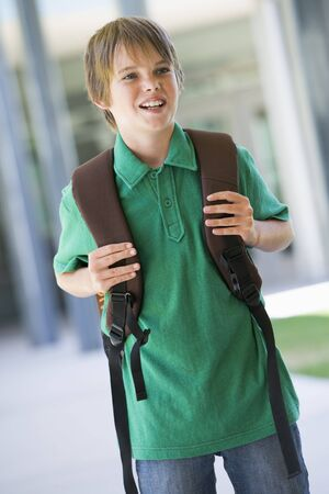 ruck sack: Student standing outside school smiling (selective focus)