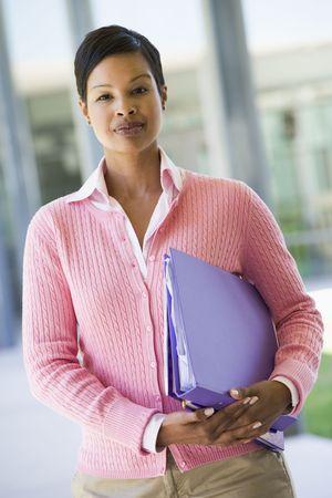 Teacher standing outside school holding binders (selective focus)