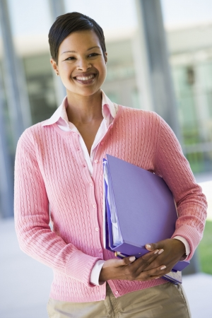 frontal portrait: Teacher standing outside school holding binders and smiling (selective focus) Stock Photo