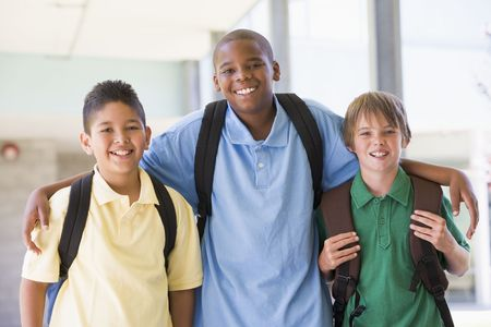 only boys: Three students standing outside school together smiling (high key) Stock Photo
