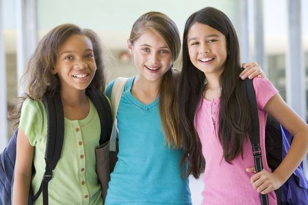 Tres estudiantes de pie fuera de la escuela junto sonriente (atención selectiva)