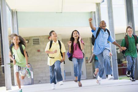 ni�os en la escuela: Seis estudiantes huyendo de la puerta principal de la escuela emocionados