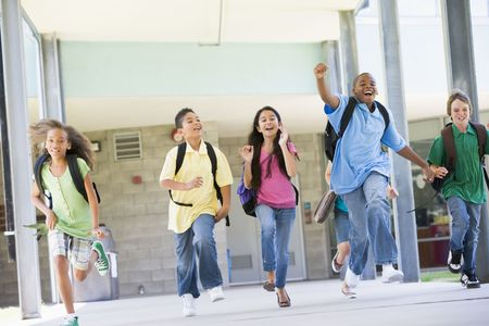 Six students running away from front door of school excited photo