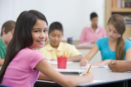 taking note: Studenti in classe prendere appunti con insegnante in background (attenzione selettiva) Archivio Fotografico