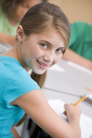 tweens: Student in class taking notes (selective focus)