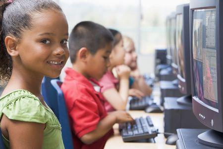 salle classe: Quatre enfants � des terminaux d'ordinateur (profondeur de champ  haute cl�)