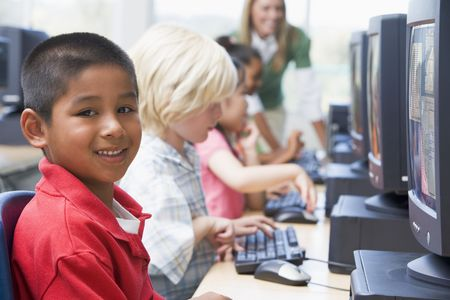 uses computer: Four children at computer terminals with teacher in background (depth of fieldhigh key)