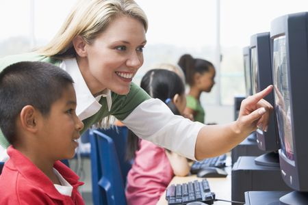 Teacher helping student at computer terminal with students in background (selective focus/high key) Stock Photo - 3205107