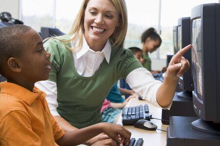 tutor: Maestro ayudar a los estudiantes a terminal de computadora con los estudiantes en el fondo (enfoque selectivo  alto clave)