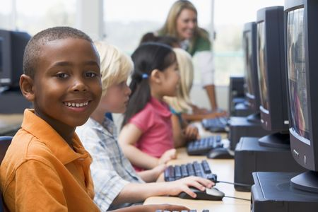 computer centers: Children at computer terminals with teacher in background (depth of fieldhigh key) Stock Photo