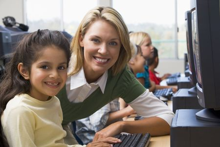 Teacher helping student at computer terminal with students in background (depth of fieldhigh key) photo