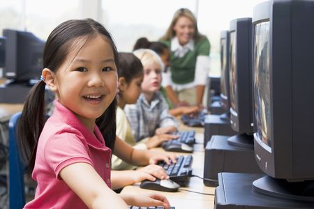 Children at computer terminals with teacher in background (depth of fieldhigh key) photo