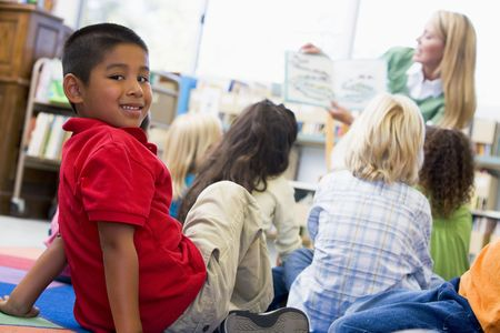 Student in class looking at camera with teacher reading in background (selective focus) Stock Photo - 3207438
