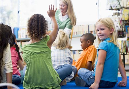 Student in class looking at camera with teacher reading in background (selective focus) photo