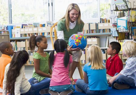 Teacher in class showing students a globe photo