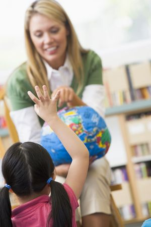 responds: Teacher in class showing a globe with student volunteering in foreground (selective focus)