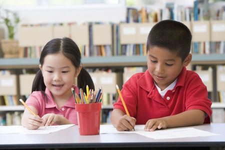 filipino ethnicity: Two students in class writing