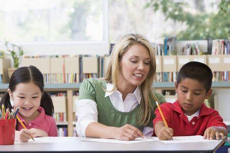 tutor: Dos estudiantes en la clase de escritura con ayuda de maestros