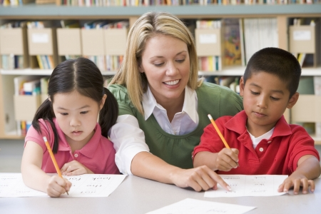 teacher: Two students in class writing with teacher helping Stock Photo