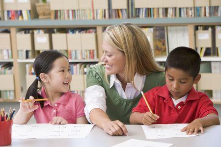 profesor alumno: Dos estudiantes en la clase de escritura con ayuda de maestros