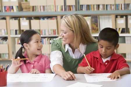 literacy instruction: Two students in class writing with teacher helping Stock Photo