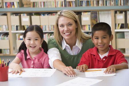 salon de clases: Dos estudiantes en la clase con profesor  Foto de archivo