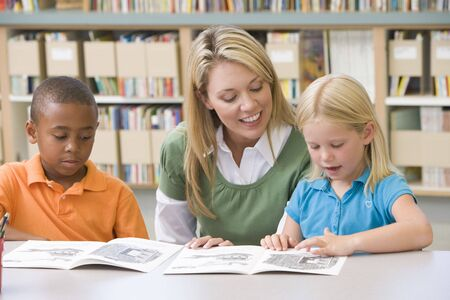 middle class: Two students in class reading with teacher