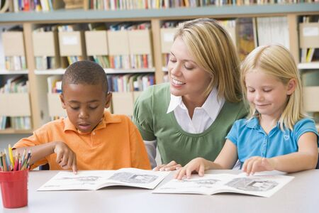 Two students in class reading with teacher Stock Photo - 3207270