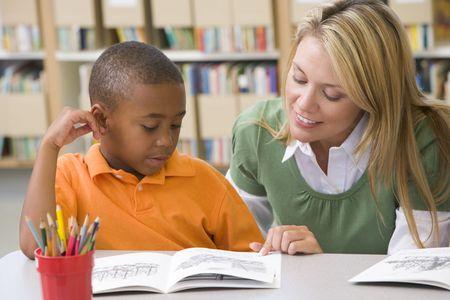 sachant lire et �crire: El�ve en classe de lecture avec des enseignants Banque d'images