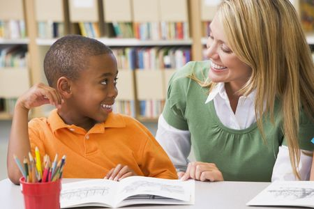 profesor alumno: Estudiante en la clase de lectura con el maestro