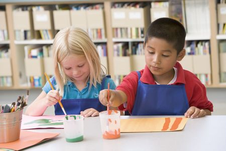 craft materials: Two students in art class painting Stock Photo