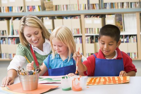 Two students in art class with teacher photo