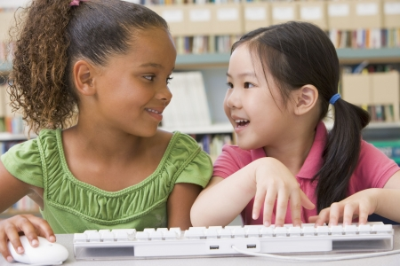 computer classroom: Two students in class at computer keyboard Stock Photo