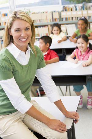 les geven: Leraar in de klas met leerlingen in de achtergrond (selectieve aandacht)