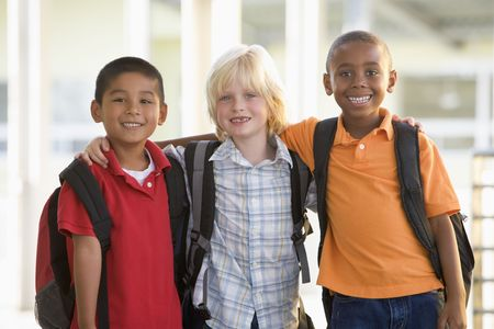 knap sack: Three students outside school standing together smiling (selective focus)