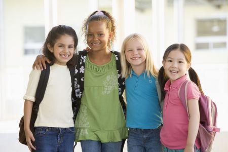 schoolchild: Vier studenten buiten de school staande samen lachend (high key) Stockfoto