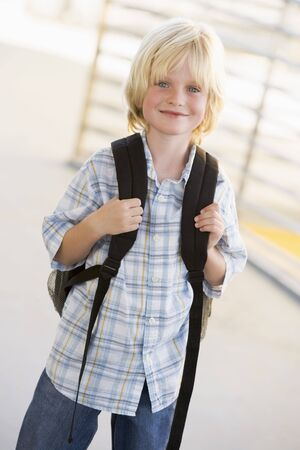 knap sack: Student standing outdoors smiling (high key) Stock Photo