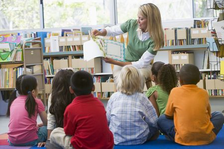 Teacher in class reading to students photo
