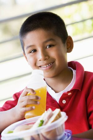 philippino: Student outdoors with lunch drinking juice (selective focus)