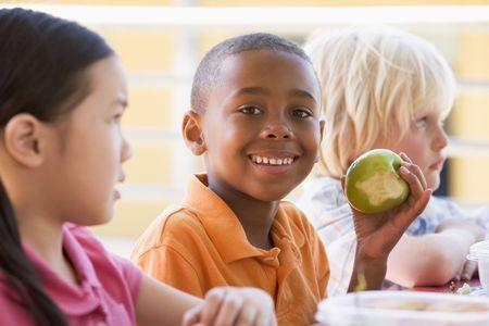 ni�os comiendo: Los estudiantes de comer el almuerzo al aire libre (atenci�n selectiva)