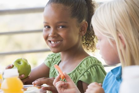 kids eating healthy: Students outdoors eating lunch (selective focus)