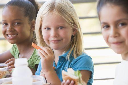 marchew: Studenci na zewnątrz jedzenia lunchu (selektywnej focus) Zdjęcie Seryjne