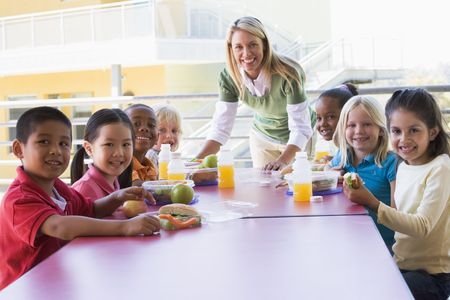 Teacher leaning on table outdoors while students eat lunch (high key) photo