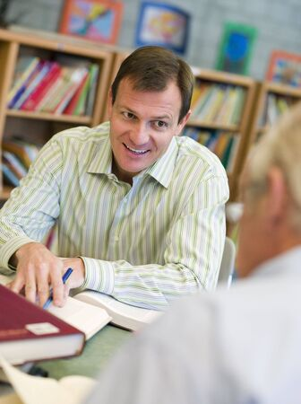 Two men in library with notepads talking (selective focus) photo