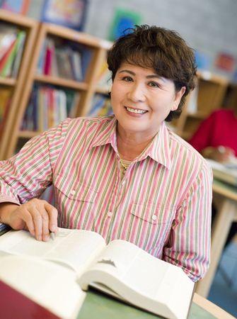 one senior adult woman: Mujer sentada en la biblioteca con un libro (enfoque selectivo)