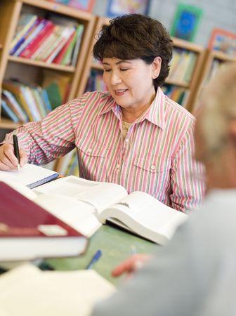 sachant lire et �crire: Homme et femme assis dans la biblioth�que de livres de lecture (s�lective focus)