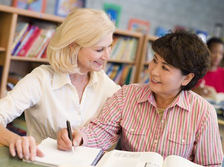 frontal views: Two women sitting in library with a book and notepad (selective focus)
