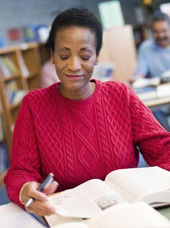 mujer alegre: Mujer sentada en la biblioteca con un libro y cuaderno (atenci�n selectiva)
