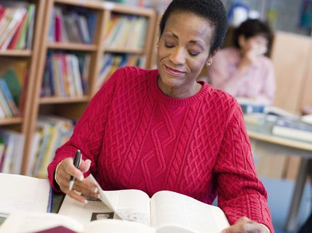 Woman sitting in library with a book and notepad (selective focus) Stock Photo - 3194553